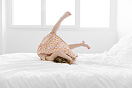 Little girl wearing summer dress doing somersault on a white bed - LITF000198