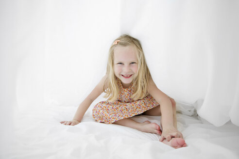 Portrait of smiling blond girl on a white bed hiding under a sheet - LITF000201
