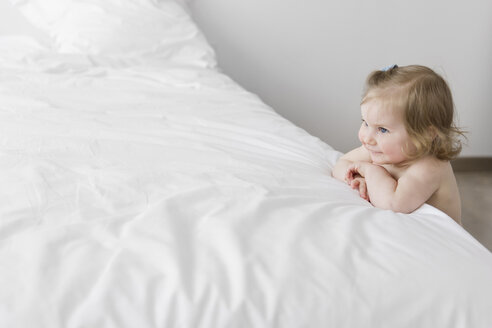 Smiling toddler girl leaning on white bed - LITF000207