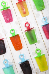Different colorful ice lollies and ice cubes on white ground - RTBF000043