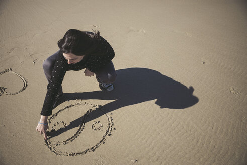 Woman scratching Yin Yang symbol in the sand of a beach - EPF000040