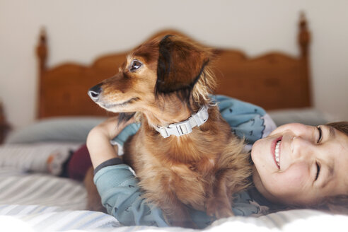 Smiling little boy lying on bed with long-haired Dachshund - VABF000381
