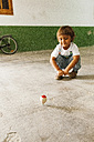 Smiling little boy watching spinning top - VABF000384