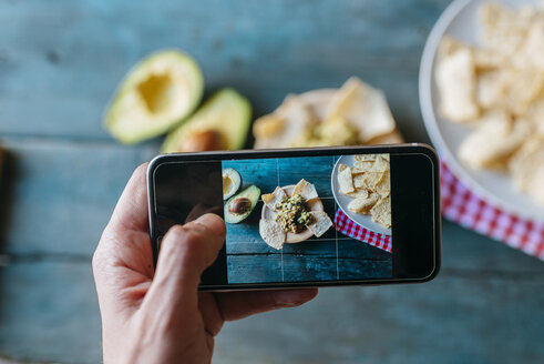 Taking a picture of nachos and guacamole with smartphone, close-up - KIJF000276
