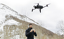 Spain, Asturias, man navigating a drone in the snowy mountains - MGOF001629