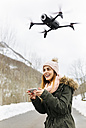 Spain, Asturias, young woman navigating a drone in the snowy mountains - MGOF001632