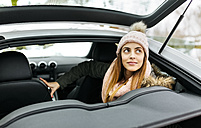 Portrait of young woman sitting in a sports car - MGOF001635