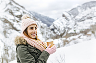 Spain, Asturias, happy young woman with coffee to go in the snowy mountains - MGOF001638