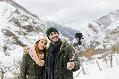 Spain, Asturias, couple taking selfie in the snowy mountains - MGOF001641