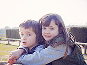 Portrait of smiling girl hugging her little brother - XCF000069