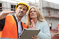 Man with hard hat talking to woman on construction site - MAEF011388