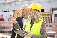 Woman with hard hat talking to man on construction site - MAEF011397