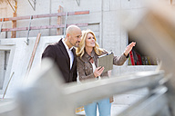Woman with digital tablet talking to man on construction site - MAEF011400