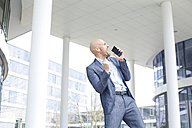 Enthusiastic businessman listening to music from smartphone - MAEF011409