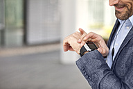 Close-up of businessman looking at smartwatch - MAEF011415
