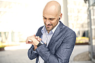 Smiling businessman with earbuds looking at smartwatch - MAEF011421