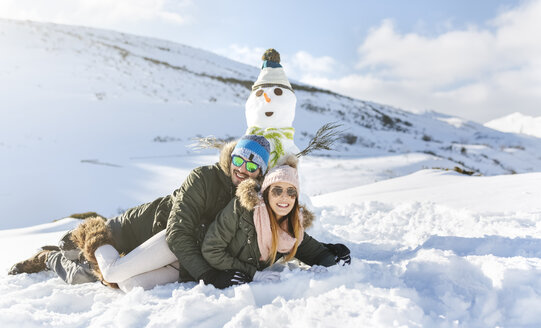 Spain, Asturias, happy couple lying in snow next to snowman - MGOF001673