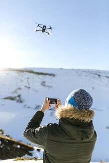 Spain, Asturias, man flying drone in snowy mountains - MGOF001679