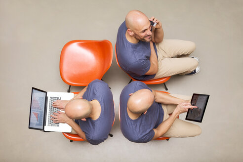 Man sitting on chairs using portable devices, multitasking - MAEF011426
