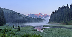 Italy, Province of Belluno, Dolomites, Misurina Lake with the Sorapiss mountain massif with morning fog - RUEF001665