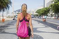 Brazil, Rio de Janeiro, back view of woman walking on pavement - MAUF000370