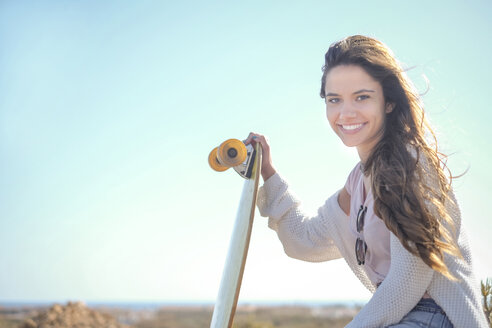 Portrait of smiling teenage girl with longboard - SIPF000292