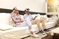 Couple sitting on couch at home using Virtual Reality Glasses - MAEF011430