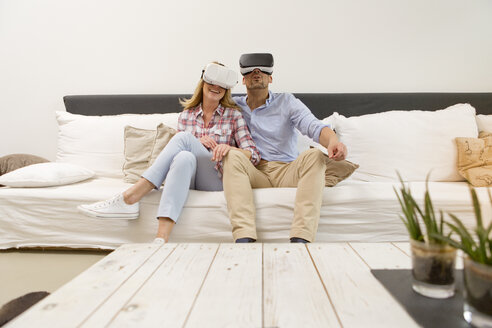 Couple sitting side by side on couch at home using Virtual Reality Glasses - MAEF011433