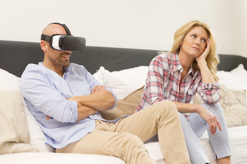 Man wearing Virtual Reality Glasses sitting on couch beside his bored wife - MAEF011436
