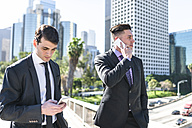 USA, Los Angeles, two businessmen using cell phones - LEF000009