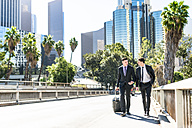 USA, Los Angeles, two businessmen walking with luggage - LEF000012