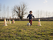 Little boy playing soccer on grass among traffic cones - XCF000070
