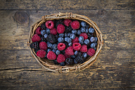 Wickerbasket of different wild berries on wood - LVF004680
