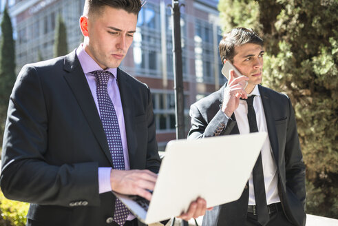 Two businessmen outdoors with laptop and cell phone - LEF000022