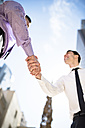 Two businessmen shaking hands outdoors - LEF000028
