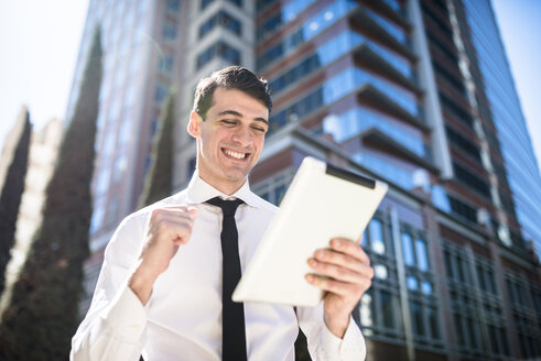Happy businessman outdoors with tablet clenching his fist - LEF000034