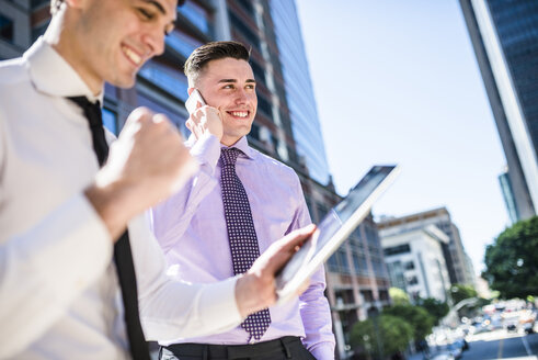 Two businessmen outdoors with tablet and cell phone - LEF000037