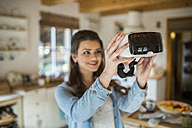 Young woman at home using Virtual Reality goggles - HAPF000328