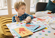 Little boy creating Easter cards with handprints at home - MFF002954