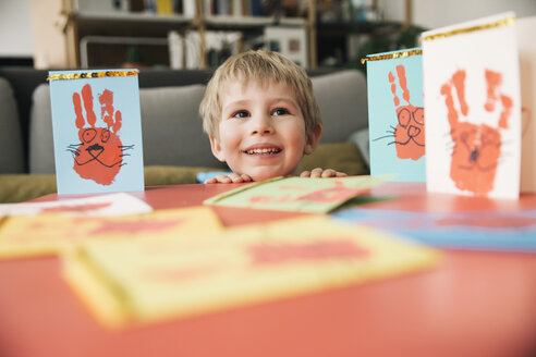 Happy little boy with self-made Easter cards at home - MFF002957