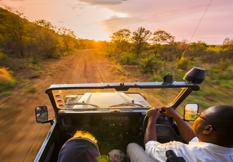 Namibia, Outjo, driving off-road vehicle at sunset in Ongava Wild Reservat - AM004818