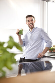 Portrait of laughing young man with green smoothie in his kitchen - MFRF000540