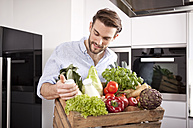 Portrait of young man with wooden box of fresh vegetables and two milk bottles in his kitchen - MFRF000546