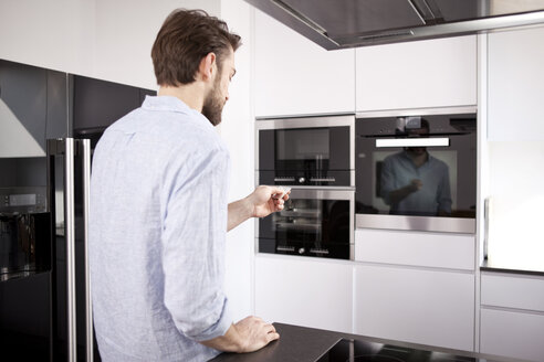 Man standing in his built-in kitchen switch on the oven with remote control - MFRF000549