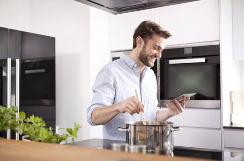 Young man looking at with mini tablet while cooking - MFRF000552