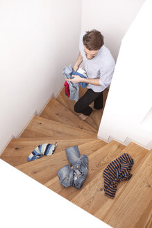 Man collecting scattered clothing on wooden stairs at home - MFRF000564