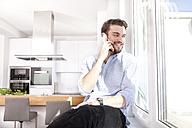 Young man sitting on window sill in his kitchen looking through window while telephoning - MFRF000567