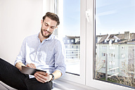 Young man sitting on sideboard near window using mini tablet - MFRF000570