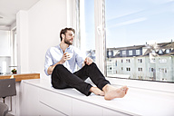 Young man with coffee cup sitting on sideboard at home looking through window - MFRF000573