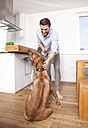 Man with his Rhodesian Ridgeback in the kitchen - MFRF000576